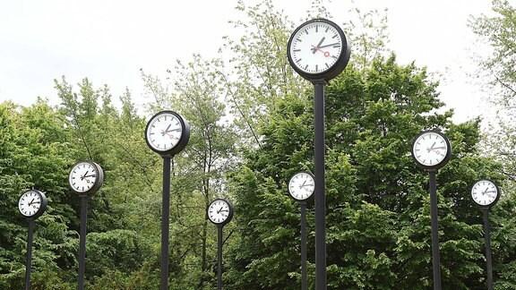 Installation aus mehreren Uhren, die auf Metallsäulen stehen und alle die gleiche Zeit anzeigen