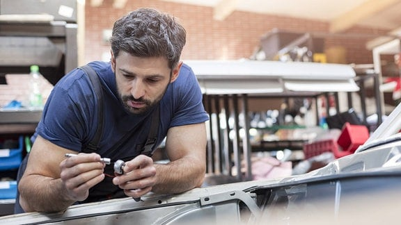 Ein Mechaniker schaut sich in einer Werkstatt ein Autoteil an.