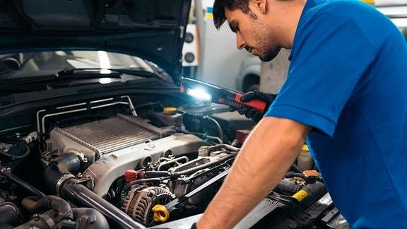 Werkstattmitarbeite vor geöffneten Motorraum