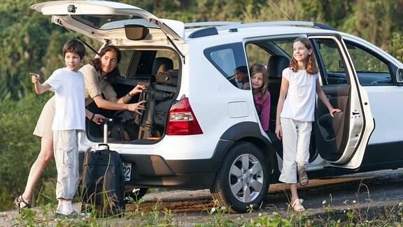 Eine Familie steigt aus dem Auto