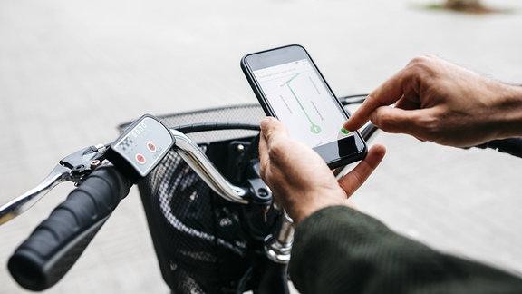 Mann mit E-Bike nutzt Navigationssystem auf Mobiltelefon.