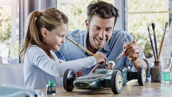 Vater und Tochter bemalen ein Modellauto