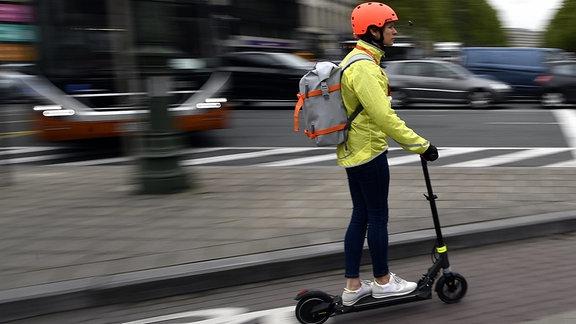 Ein Frau fährt auf einem E-Tretroller auf einem Fahrradweg.