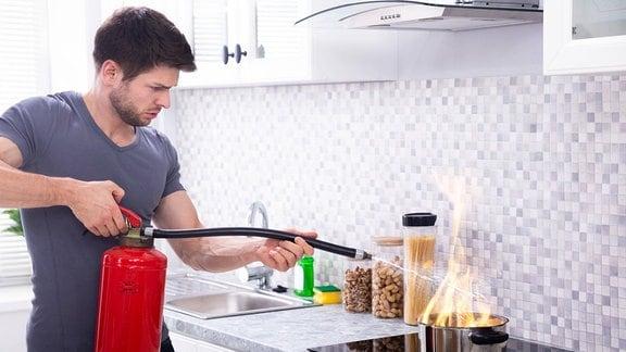 Ein Mann löscht Feuer in einem Kochtopf.