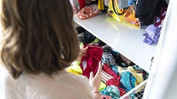 Eine Frau vor einem geöffneten Kleiderschrank hat ein Kleidungsstück in Händen