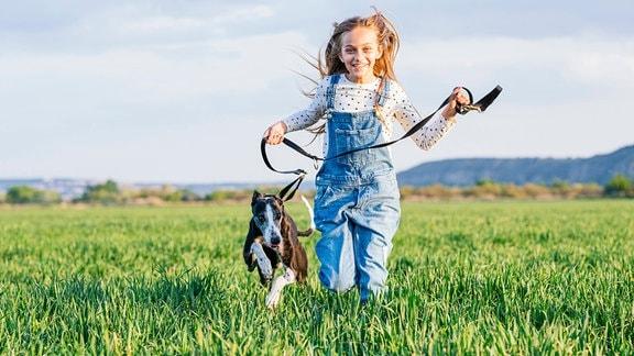 ein Mädchen läuft mit ihrem Hund über eine Wiese