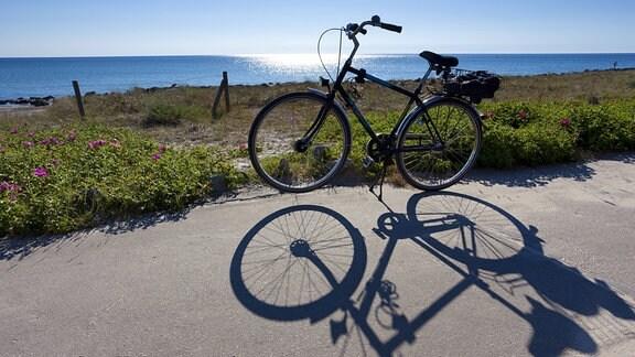 Fahrrad wirft Schatten an der Ostsee