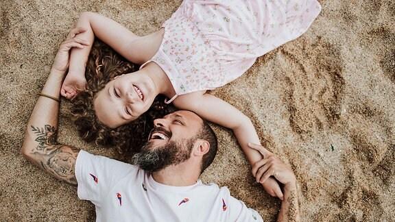 Ein Mann und ein Mädchen im Sand