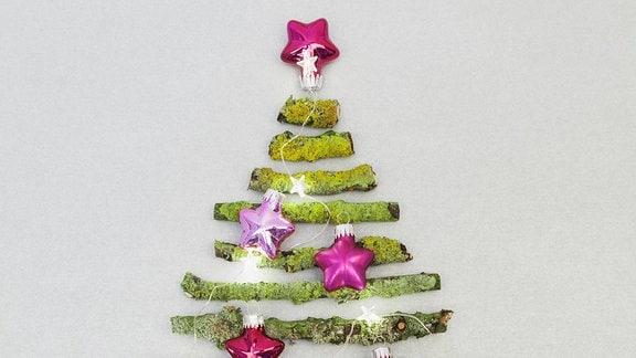 Äste mit Moos in Weihnachtsbaum Form an Wand mit Dekokugeln.