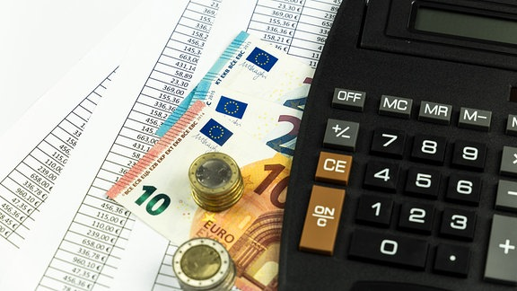 Ein Taschenrechner liegt neben Bargeld auf ausgedruckten Tabellen.