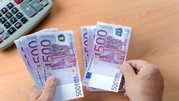 mehrere fünfhunderter Geldscheine und ein Taschenrechner