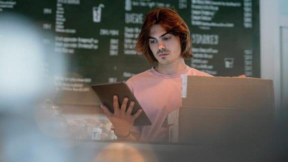 Ernst blickender Ladenbesitzer hat eine Kiste vor sich auf dem Tresen und einen Tablet-PC in der hand