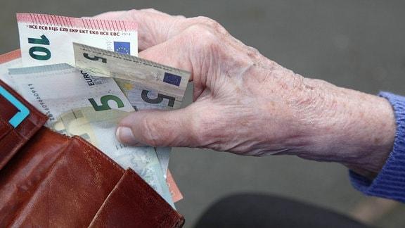 Eine Seniorin haelt Geldscheine in ihrer Hand.