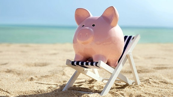 Symbolfoto - Ein Sparschwein hockt auf einem Strandkorb.