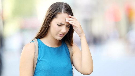 Frau hat Schwindelgefühl in verschwommener Einkaufsstraße und hält sich die Stirn