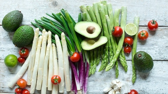 Verschiedenes Gemüse und Früchte liegen auf einem weißen Holztisch.