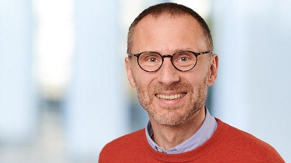 Prof. Alfred Simon, Leiter der Geschäftsstelle der Akademie für Ethik in der Medizin e. V., Göttingen, mit rotem Pullover und hellblauem Hemdkragen, lächelt in die Kamera. Er trägt Drei-Tage-Bart, kurze braune Haare und eine runde Brille.