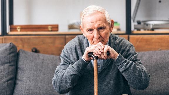 Ein älterer Mann sitzt auf dem Sofa