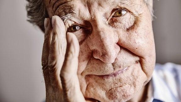Senior hält sich Hand an das Gesicht