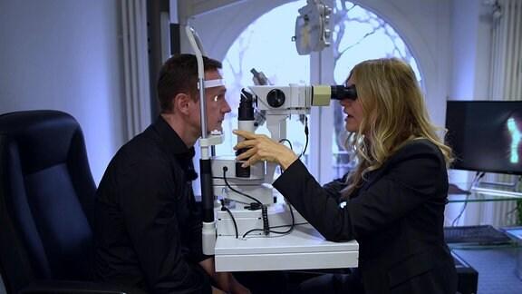Mann bei Untersuchung der Augen beim Optiker
