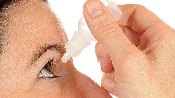 Eine Frau hält sich Augentropfen über ein Auge