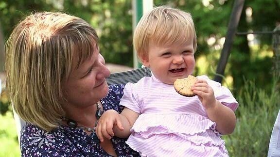 Fröhliches Kleinkind mit Keks in der Hand auf dem Arm einer Frau