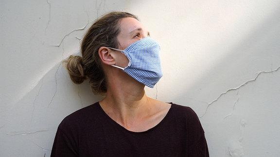 Eine Frau mit Mund-Nasen-Schutz vor einer Wand