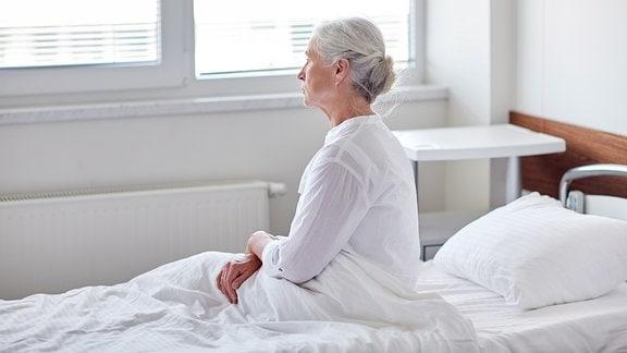 Seniorin sitzt auf Krankenhausbett