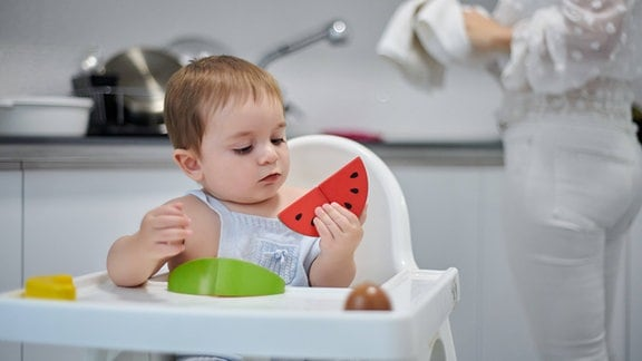 Kind mit Spielzeugfrüchten sitzt auf Hochstuhl