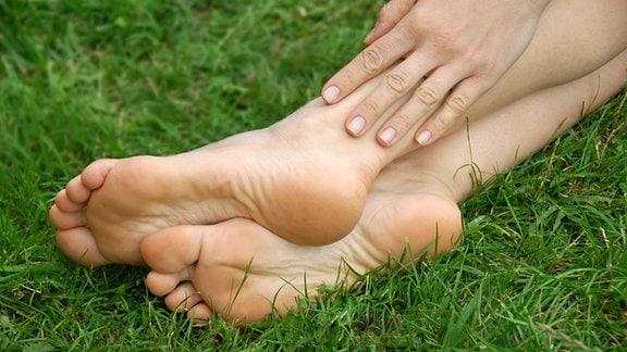 Füße und Hand einer Frau auf grünem Gras