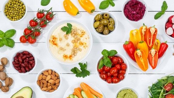 Verschiedene Gemüse, Salate und Nüsse auf einem Tisch