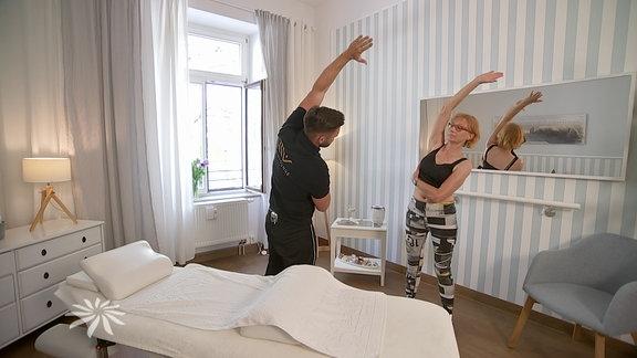 Ein Mann und eine Frau machen Gymnasikübungen in einer Wohnung