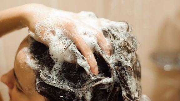 Frau unter der Dusche bei der Haarwäsche