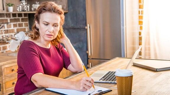 Frau arbeitet im Homeoffice an einem Schreibtisch.