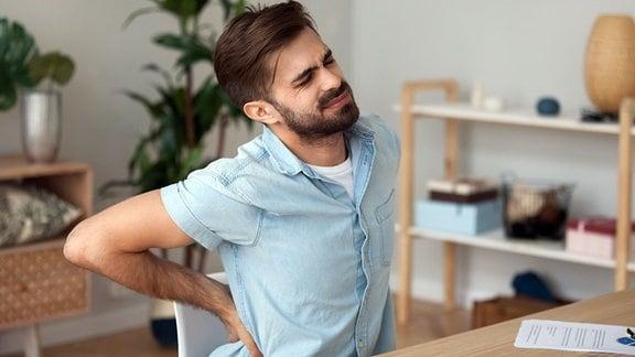 Mann mit Rückenschmerzen am Schreibtisch