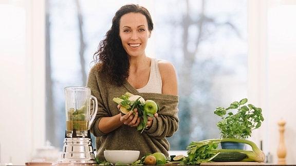 Eine junge Frau steht in einer Küche und hat verschiedene Gemüsesorten in der Hand