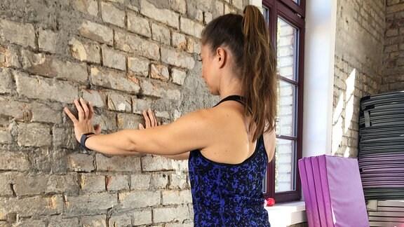 Sabine Schön zeigt einen Liegestütz an der Wand