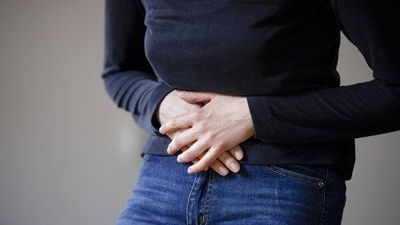 Symbolfoto Magenschmerzen. Eine Frau haelt ihre Haende vor den schmerzenden Bauch