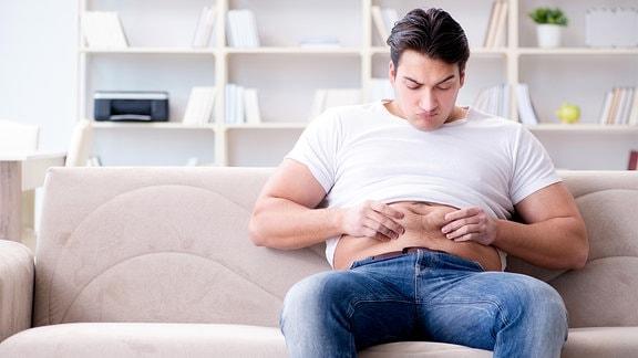 Mann sitzt auf dem Sofa und kneift sich in den Bauch, da er zugenommen hat.