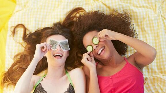 Zwei Freundinnen liegen auf dem Bett und benutzen Schönheitsprodukte