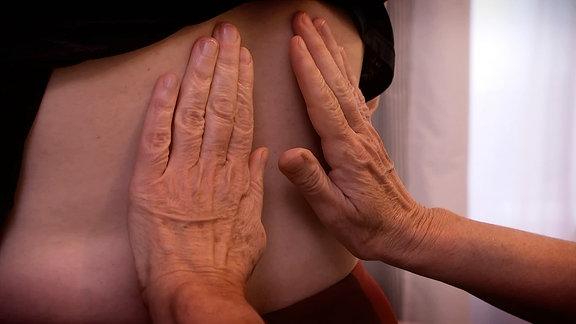 Eine Person legt die Hände auf den Rücken einer anderen Person.