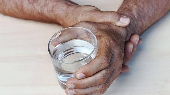 Die Hände eines Mannes mit Parkinson halten ein Wasserglas