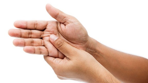 Ein Mann hält sich die schmerzende Hand.