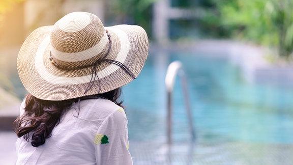 Frau mit Sonnenhut an einem Pool