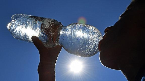Junge trinkt Wasser aus einer Plastikflasche.