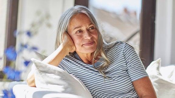 Eine Frau mit langen grauen Haaren sitzt auf einem Sofa.