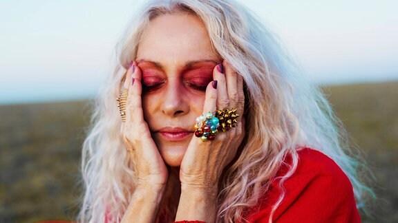 Eine Frau mit graublonden Haaren und extravaganter Schminke legt ihre Hände an die Schläfen.
