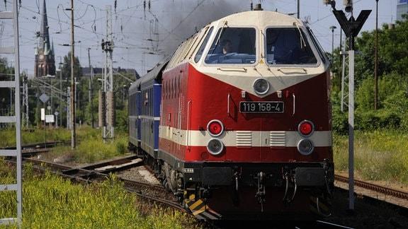 Diesellok 119 158-4 der Deutschen Reichsbahn der DDR mit Personenwagen bei einer Nostalgiefahrt am Bahnhof Berlin-Lichtenberg