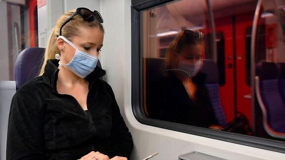 Eine junge Frau sitzt mit Smartphone und Mundschutz im Zug.