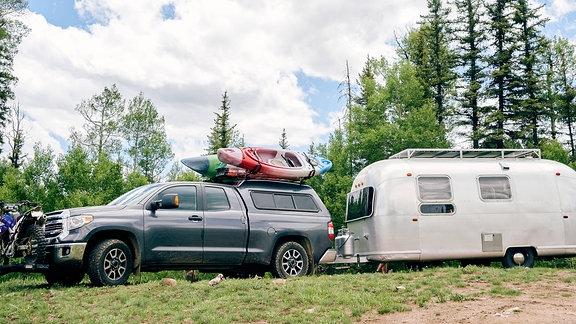 Auto mit Campinganhänger parkt vor schöner Landschaft